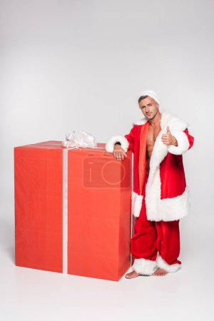 handsome santa claus leaning at big gift box and showing thumb up on grey