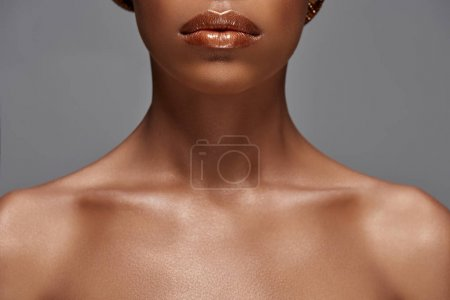 partial view of african american woman with bare shoulders isolated on grey