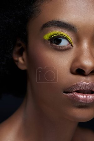 partial view of african american model with bright neon eye shadow isolated on black