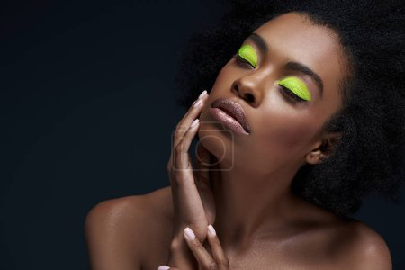 portrait of beautiful african american model with bright neon makeup and bare shoulders isolated on black