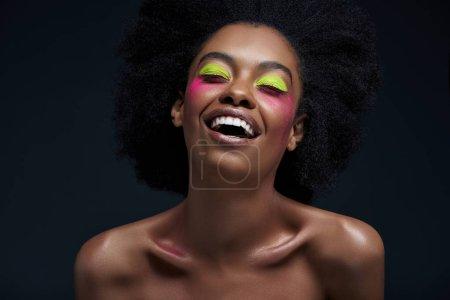 Photo pour Heureux modèle afro-américain avec néon lumineux maquillage posant isolée sur fond noir - image libre de droit