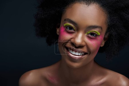 portrait of cheerful african american model with bright neon makeup posing isolated on black