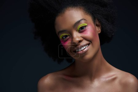 portrait of smiling african american model with bright neon makeup posing isolated on black
