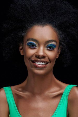 portrait of smiling african american model with bright blue eyes shadows isolated on black