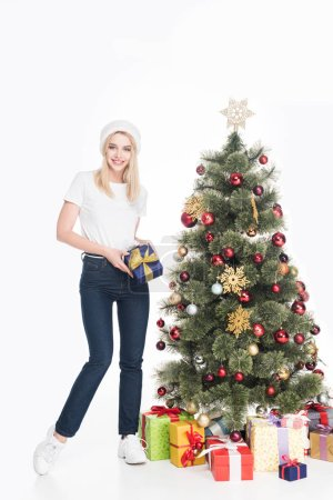 young woman in santa claus hat with wrapped gift near christmas tree isolated on white