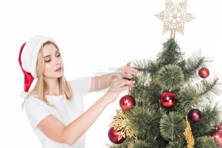 woman in santa claus hat decorating christmas tree isolated on white