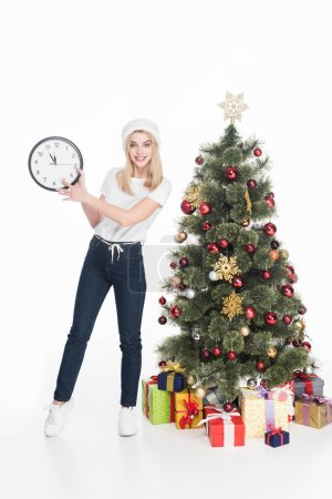 smiling woman in santa claus hat holding clock near christmas tree isolated on white