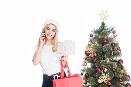 Photo pour Portrait de femme en chapeau de père Noël avec des sacs à provisions parler sur smartphone près de Noël arbre isolé sur blanc - image libre de droit