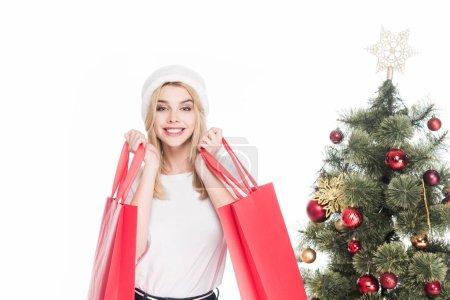 Portrait de femme souriante au chapeau de père Noël avec des sacs à provisions près de Noël arbre isolé sur blanc