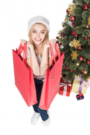 Photo for High angle view of smiling woman in santa claus hat with shopping bags near christmas tree isolated on white - Royalty Free Image