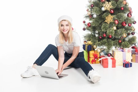 smiling woman in santa claus hat with laptop sitting near christmas tree on white background