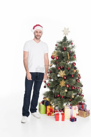 young man in santa claus hat standing near christmas tree isolated on white