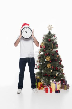 obscured view of man in santa claus hat with clock standing near christmas tree isolated on white