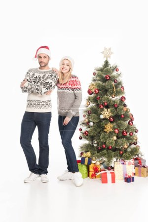 couple in sweaters and santa claus hats standing near christmas tree isolated on white
