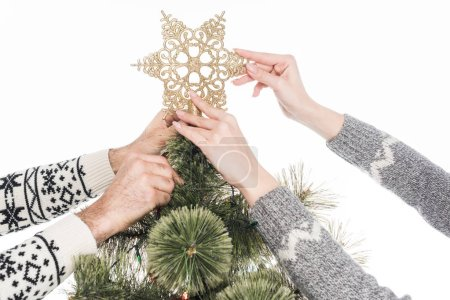 cropped shot of couple decorating christmas tree together isolated on white
