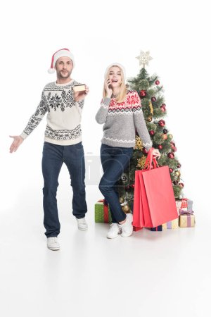 couple in sweaters and santa claus hats with shopping bags near christmas tree isolated on white