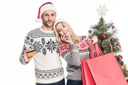 young couple in sweaters and santa claus hats with shopping bags and credit card near christmas tree isolated on white