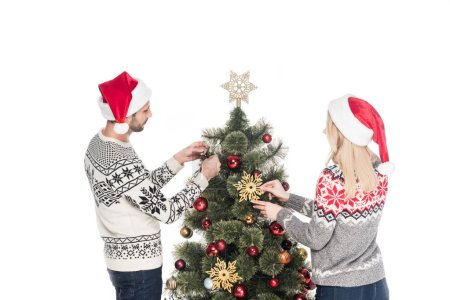 Foto de Vista posterior de la novia y novio en suéteres decoración árbol de Navidad juntos aislado en blanco - Imagen libre de derechos