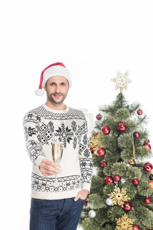 portrait of man in sweater and santa claus hat with glass of champagne standing near christmas tree isolated on white
