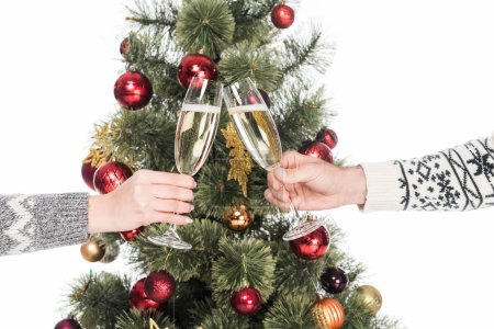 cropped shot of couple clinking glasses of champagne with christmas tree on background isolated on white