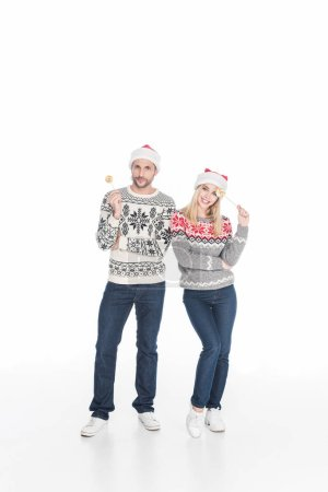 caucasian couple in santa claus hats with lollipops isolated on white