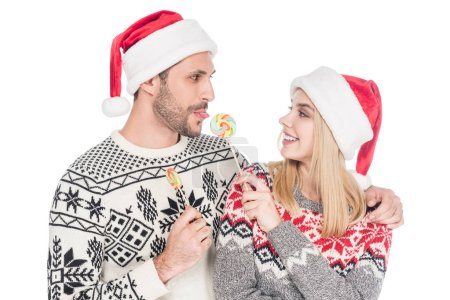 portrait of young caucasian couple in santa claus hats with lollipops isolated on white