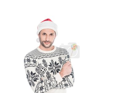 Photo for Portrait of man in sweater and santa claus hat holding lollipop isolated on white - Royalty Free Image
