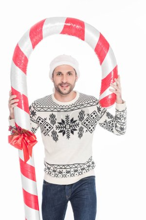 portrait of young man in sweater and santa claus hat with toy candy isolated on white