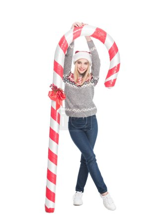 young woman in sweater and santa claus hat holding toy candy isolated on white