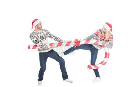 young couple in santa claus hats and sweaters pulling over toy candy isolated on white