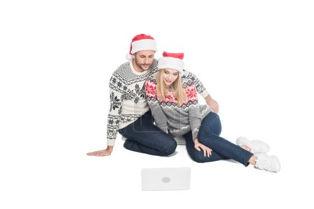 young couple in sweaters and santa claus hats with laptop isolated on white