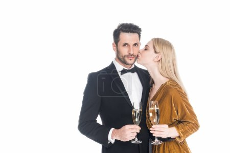 Photo for Portrait of stylish woman kissing boyfriend with glass of champagne isolated on white - Royalty Free Image