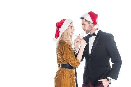 side view of stylish couple in santa claus hats drinking champagne isolated on white