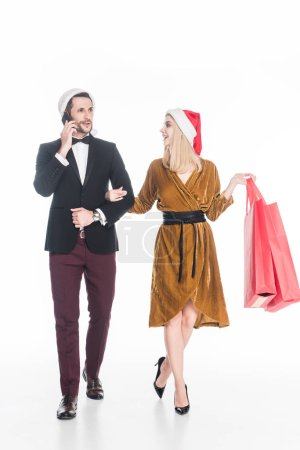 attractive man talking on smartphone near girlfriend in santa claus hat with shopping bags isolated on white