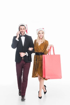 Photo for Attractive man talking on smartphone near girlfriend in santa claus hat with shopping bags isolated on white - Royalty Free Image