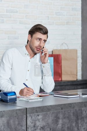 Photo for Young man talking by smartphone and writing in notebook while working in store - Royalty Free Image