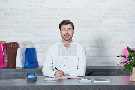 Photo for Handsome young salesman smiling at camera while working in store - Royalty Free Image