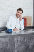 smiling young salesman talking by smartphone and looking away while working in store