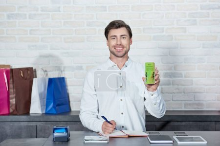 Photo for Handsome male seller holding smartphone with best shopping application and smiling at camera in store - Royalty Free Image