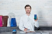 handsome male seller holding smartphone with booking application and smiling at camera in store