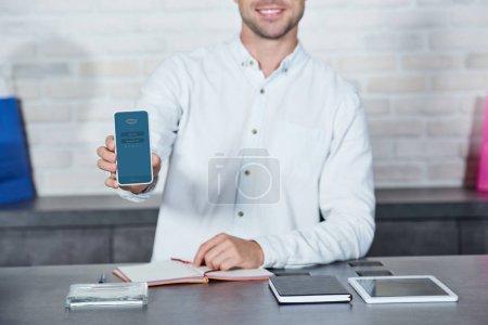 Photo pour Photo recadrée de souriant vendeur masculin maintenant smartphone avec l'application Skype en magasin - image libre de droit