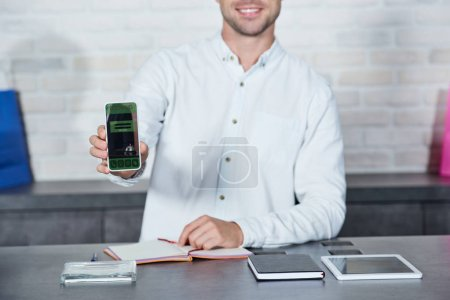 Photo pour Recadrée tir de souriant vendeur jeune maintenant smartphone avec l'application de réservation en magasin - image libre de droit