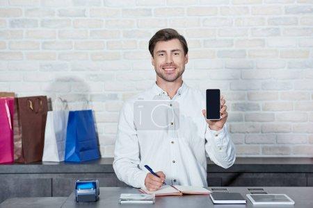 Photo pour Beau vendeur jeune tenant smartphone avec écran blanc et souriant à la caméra à la boutique - image libre de droit