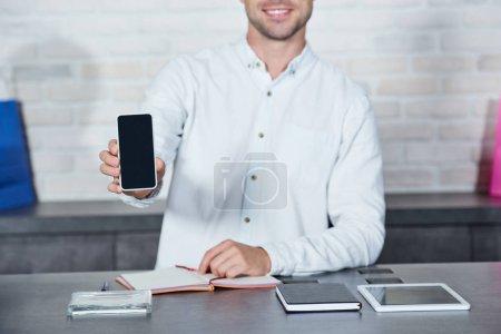 Photo pour Plan recadré de jeune vendeur souriant tenant smartphone avec écran blanc dans la boutique - image libre de droit