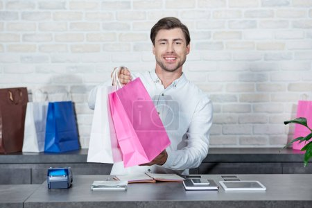 Photo for Handsome young salesman holding shopping bags and smiling at camera in store - Royalty Free Image