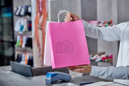 Photo for Partial view of young salesman holding paper bags in shop - Royalty Free Image