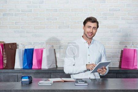 Photo pour Beau vendeur jeune à l'aide de tablette numérique et souriant à la caméra à la boutique - image libre de droit