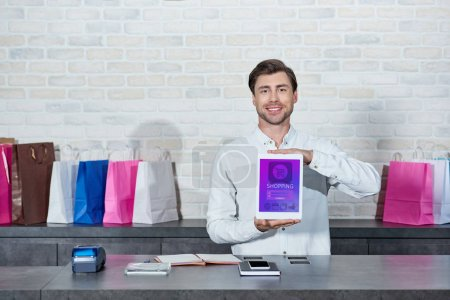 Photo for Handsome young salesman holding digital tablet with shopping application and smiling at camera in shop - Royalty Free Image