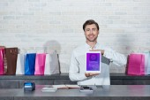 handsome young salesman holding digital tablet with shopping application and smiling at camera in shop