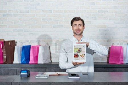 Foto de Vendedor joven guapo sosteniendo tableta digital con el uso de ebay y sonriendo a cámara en tienda - Imagen libre de derechos